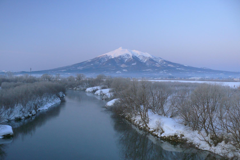 鶴寿橋の上からみる冬の岩木山と岩木川。この寒さを乗り切ってリンゴの木は花を咲かせる。土手沿いには鶴寿公園や桜づつみ公園・運動公園などがある。